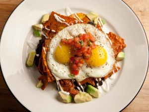 Chilaquiles rojos (triangle sliced and fried tortilla with red salsa)