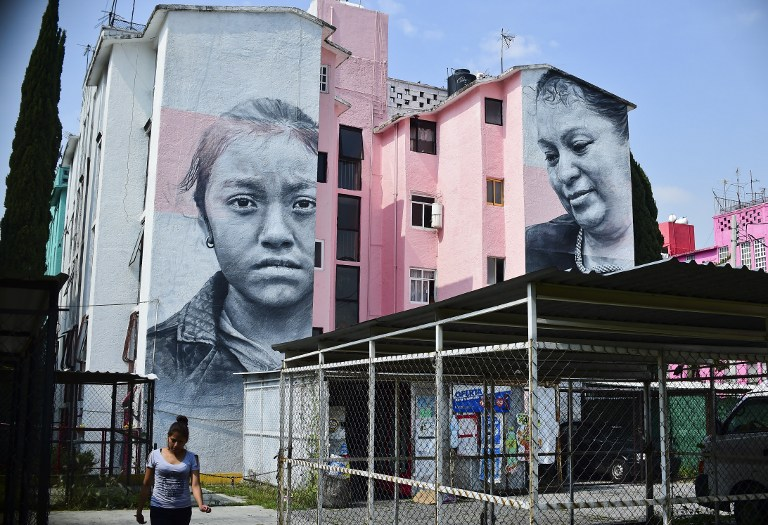 View of building decorated with a mural of Icelandic artist Guido Van Helten  at a poor neighborhood in Ecatepec, Mexico on August 25, 2016.  Dozens of murals were painted on buildings in a poor neighborhood in Ecatepec, on the route of a new cable car that will run this year. / AFP PHOTO / RONALDO SCHEMIDT / TO GO WITH AFP STORY BY JENNIFER GONZALEZ